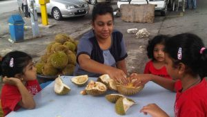 family eating durians by the roadside